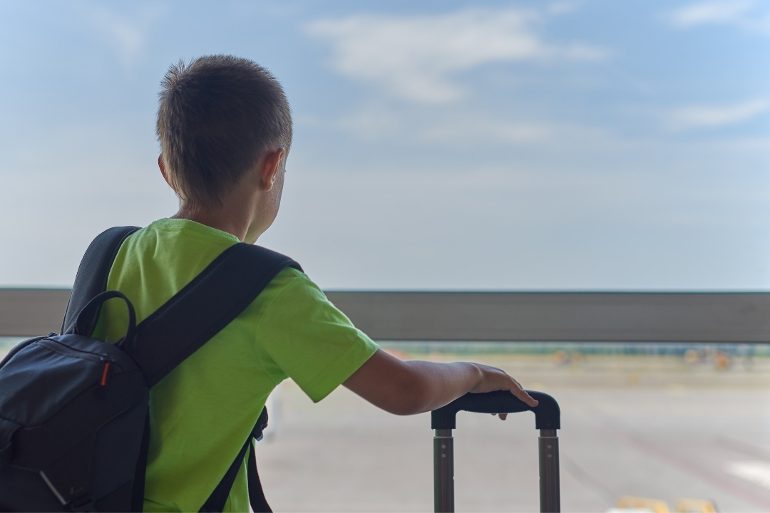 Child standing at airport with suitcase alone - unaccompanied minor policies