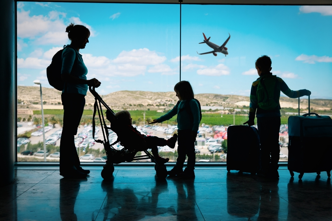 Family at airport with strollers and suitcases
