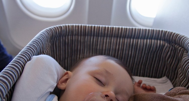 Baby sleeping in an airline bassinet