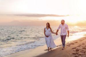 pregnant woman couple walking along beach babymoon