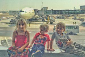 3 children sitting in an airport