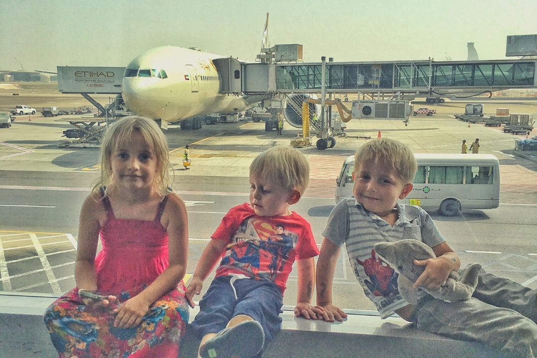 3 children sitting in an airport