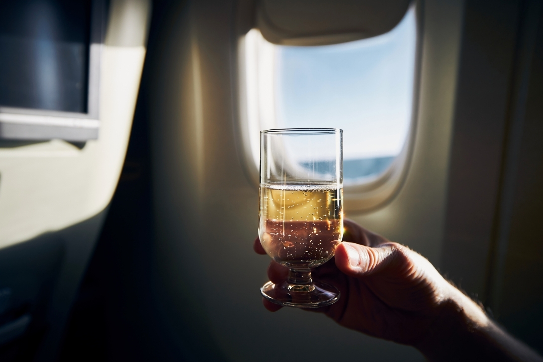Holding up a glass of champagne flying alone in business class on a plane
