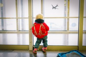 Toddler standing in airport window with a backpack - packing toddlers plane bags