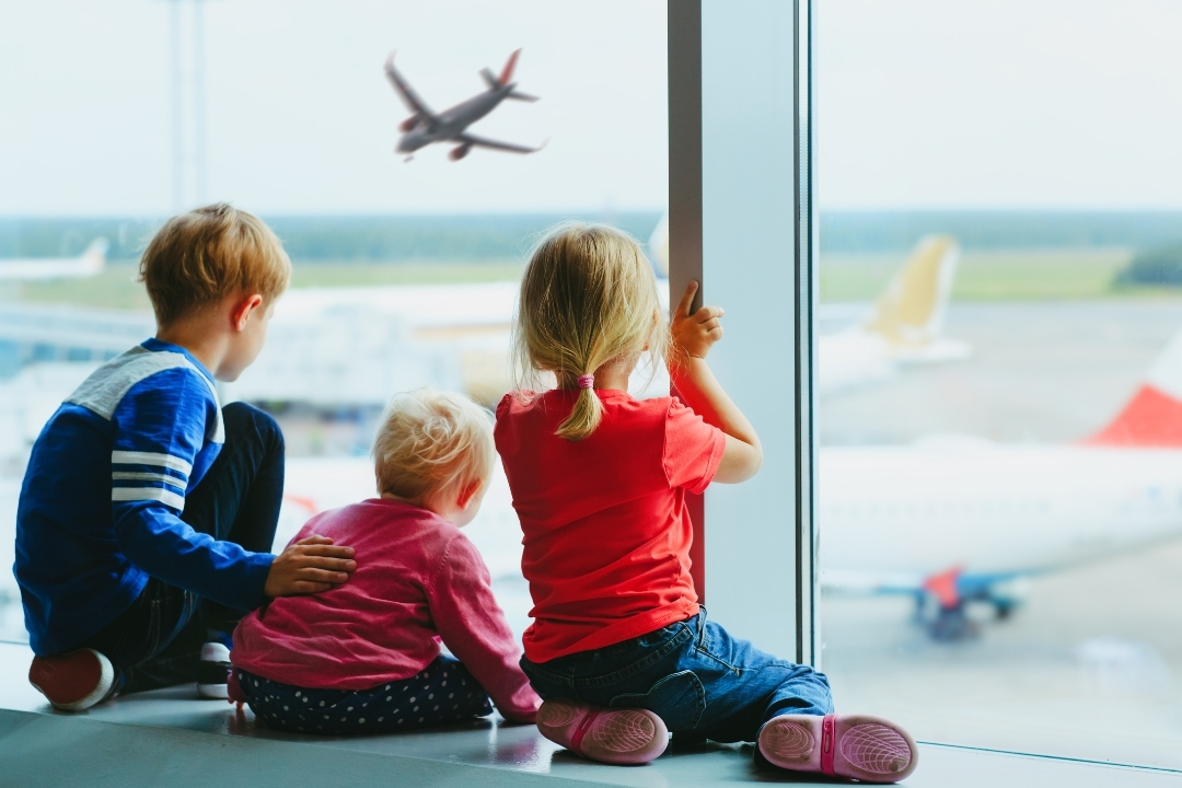 three kids sitting in an airport window waiting for flight