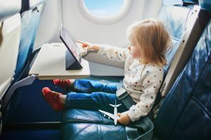 toddler sitting on a plane with a tablet and small toy plane