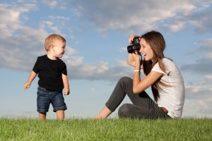 Lady photographing small child
