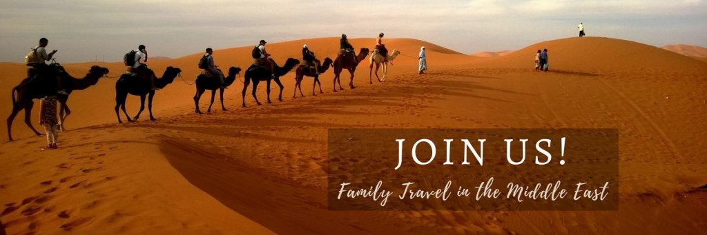 Camels walking in the desert invitation to join Facebook Group Family Travel in the Middle East