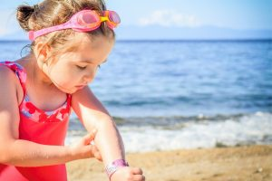 Child looking at pain in their arm - travel health