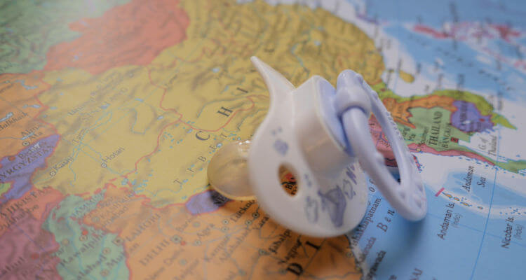 Baby's pacifier on world ma; travel related gifts for the parent to be