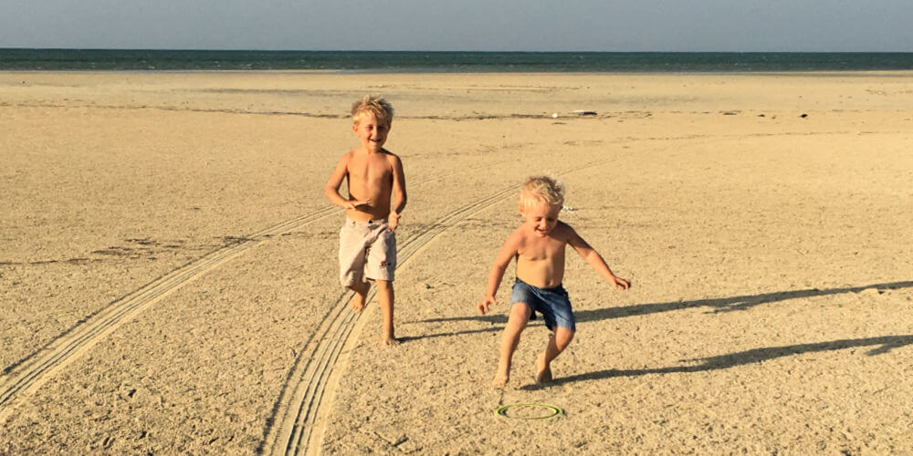 Boys playing on an open beach - beach camping essentials