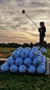 Girl practising to swing golf club