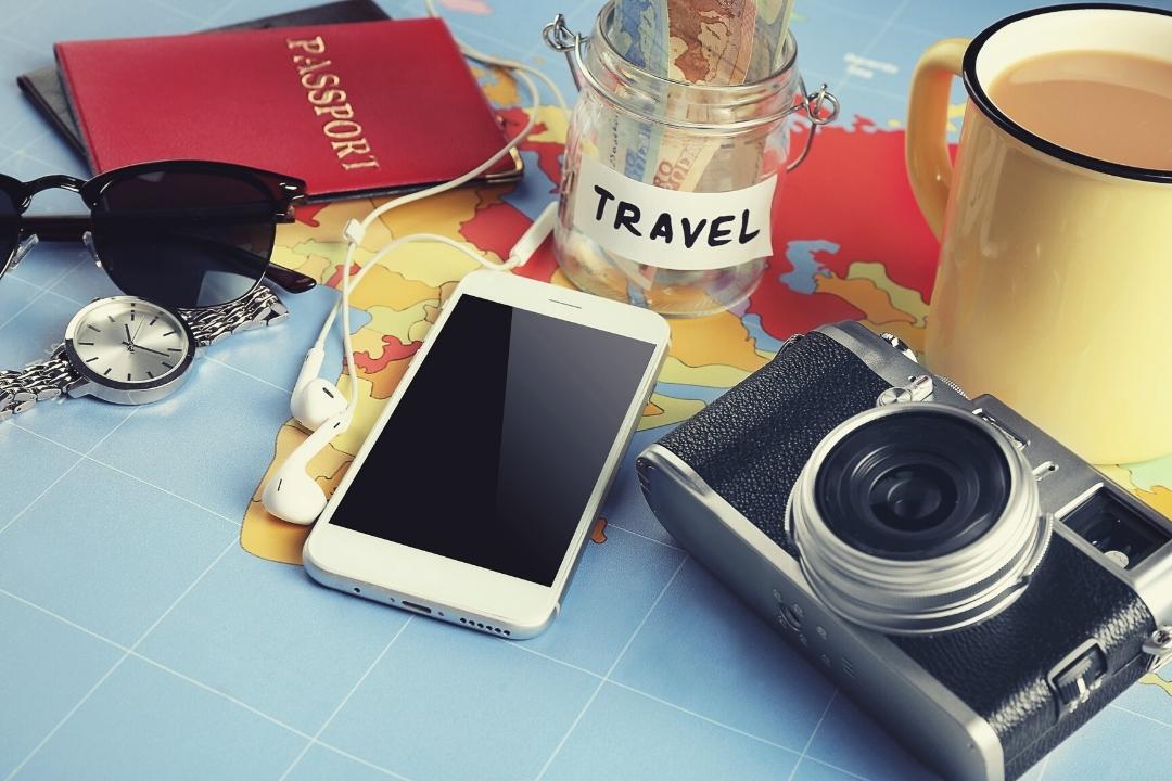Phone camera and travel saving money jar on map of the world