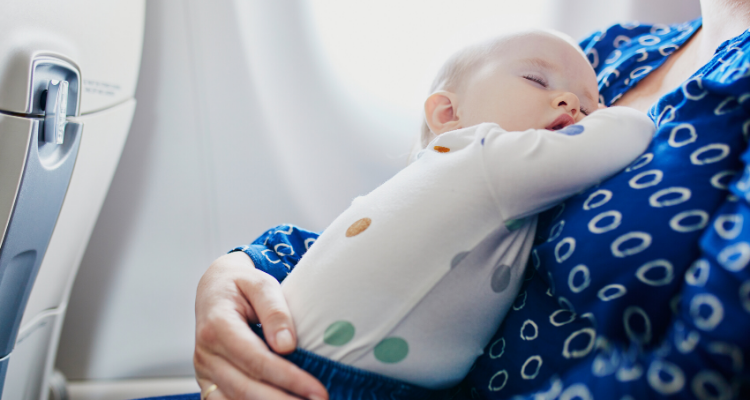 baby sleeping on mother on airplane
