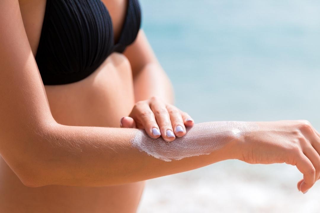 ALdy in bikini applying sun screen to protect skin