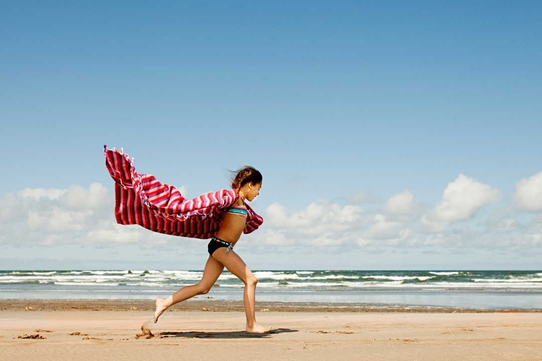 Child running along beach with large beach blanket