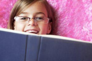 Child hiding behind a book wearing prescription glasses