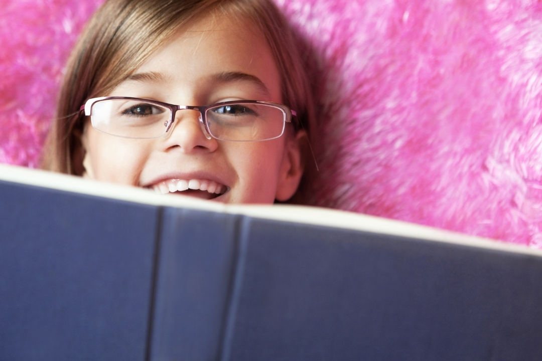 Child hiding behind a book wearing prescription glasses