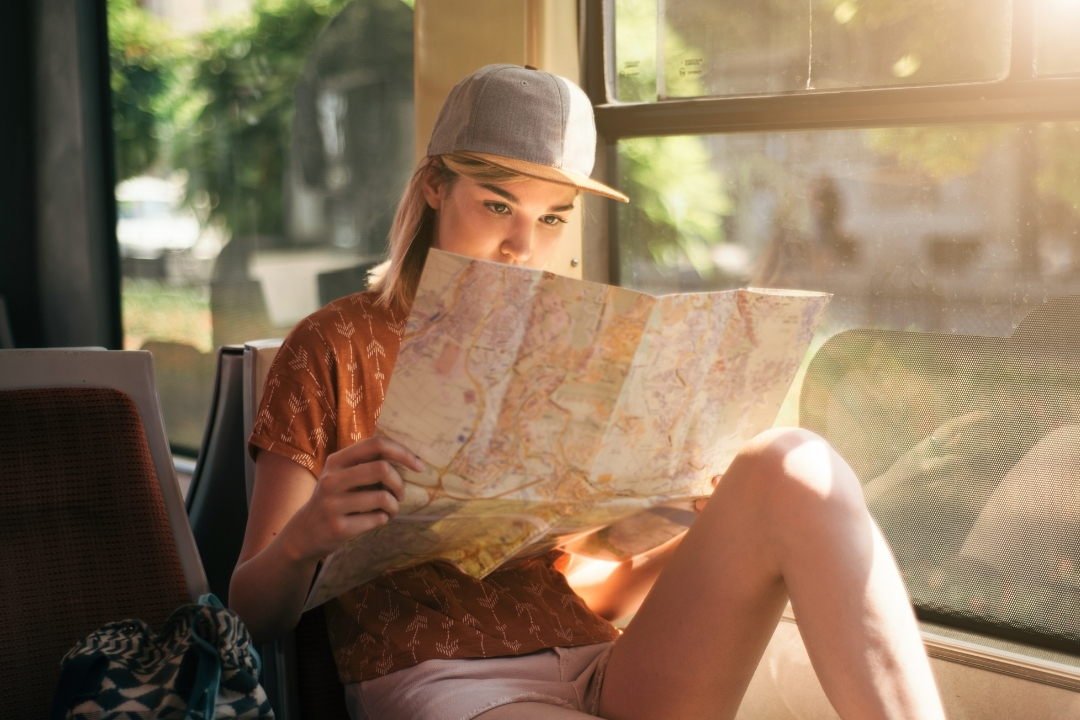 Young female student on train reading a map