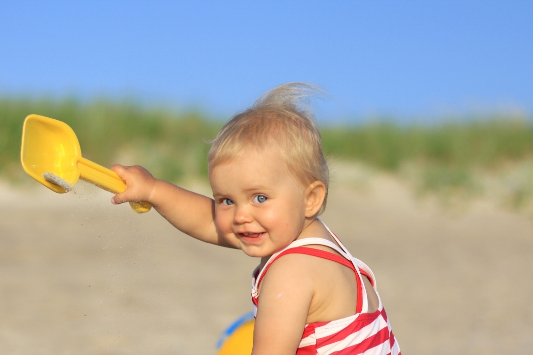 Baby on a beach playing with sand toys