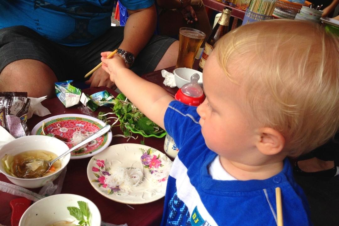 Toddler eating street food in Hanoi Vietnam