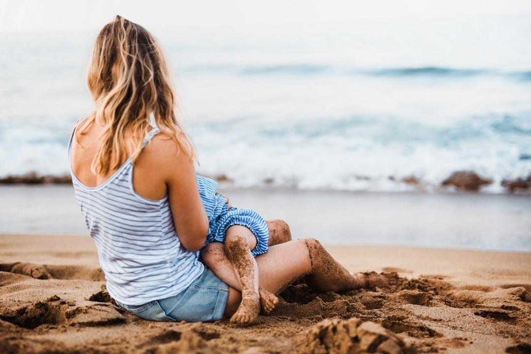 women breastfeeding a baby on the beach