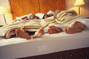 Family sleeping in hotel bed feet sticking out of bed