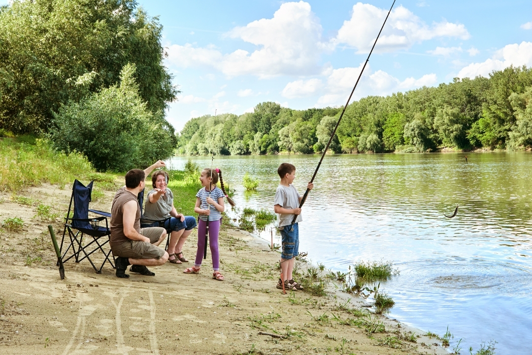 Family fishing on a river bank