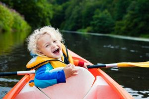 Toddler smiling and happy in a kayak