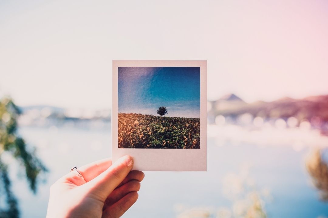person holding a polaroid photo in front of view - travel memories