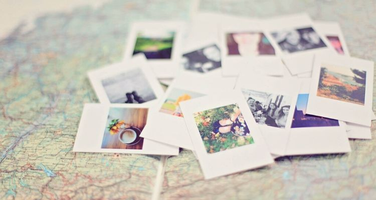 pile of polaroid style prints on a map