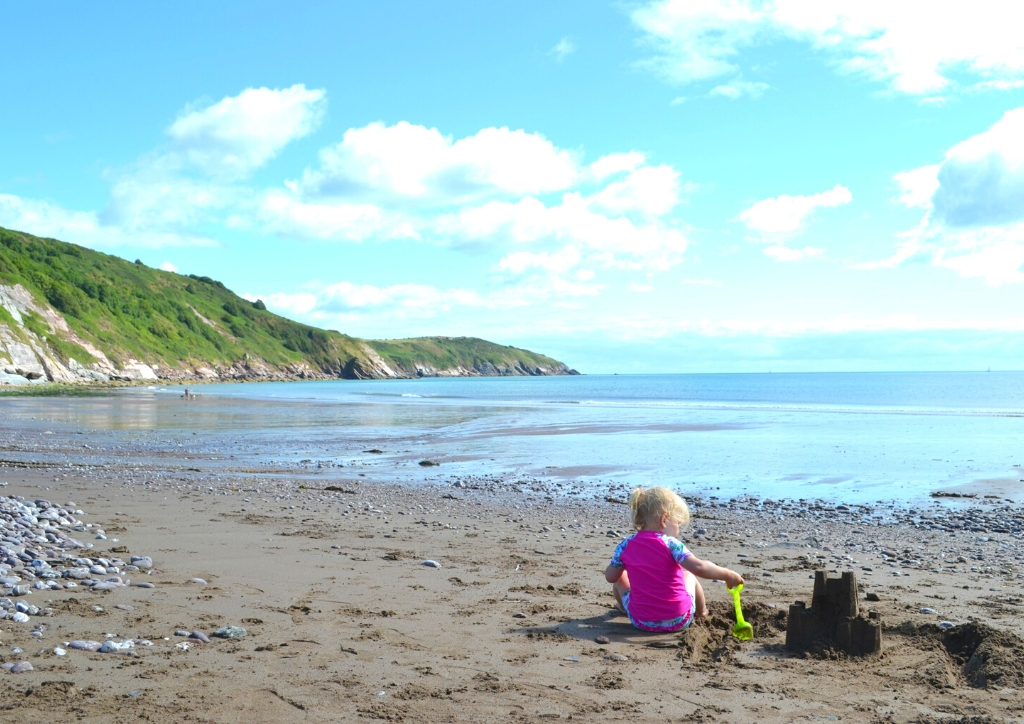 A beach in Devon UK with a small child playing
