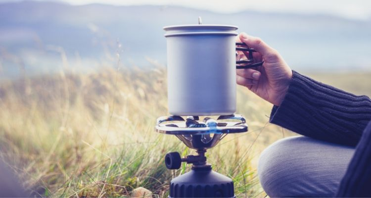 Camping stove hand holding pot