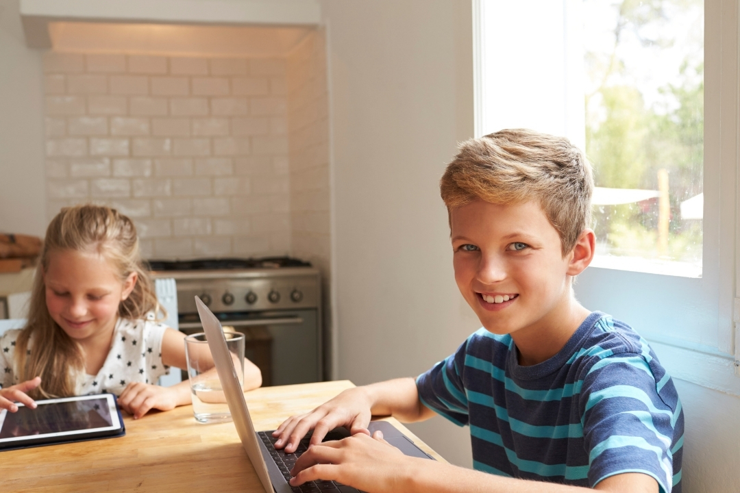 children at the kitchen table with computers - dealing with distane from family during the pandemic