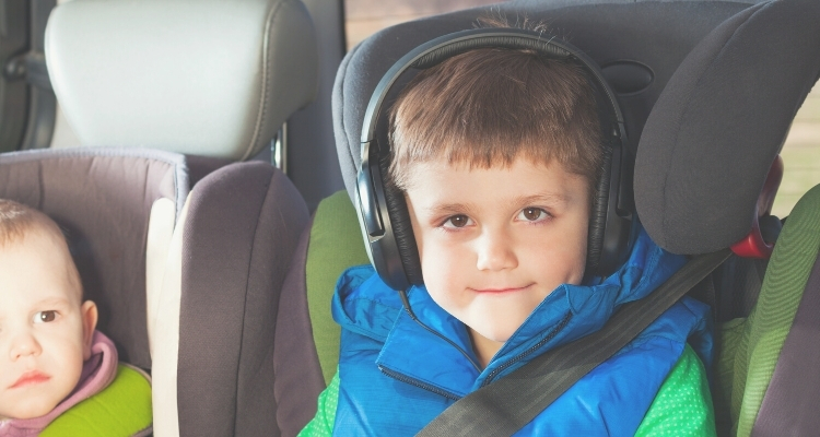 boy in car seat with headphones on listening to an audiobook