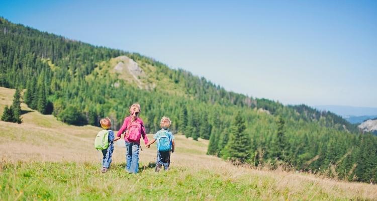 Kids holding hands walking through field