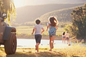 Kids running towards water, stopping on a family road trip