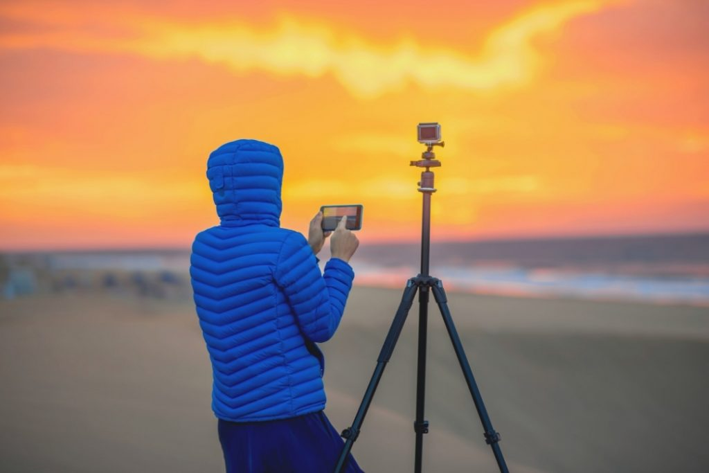 photographer with tripod videoing a sunset