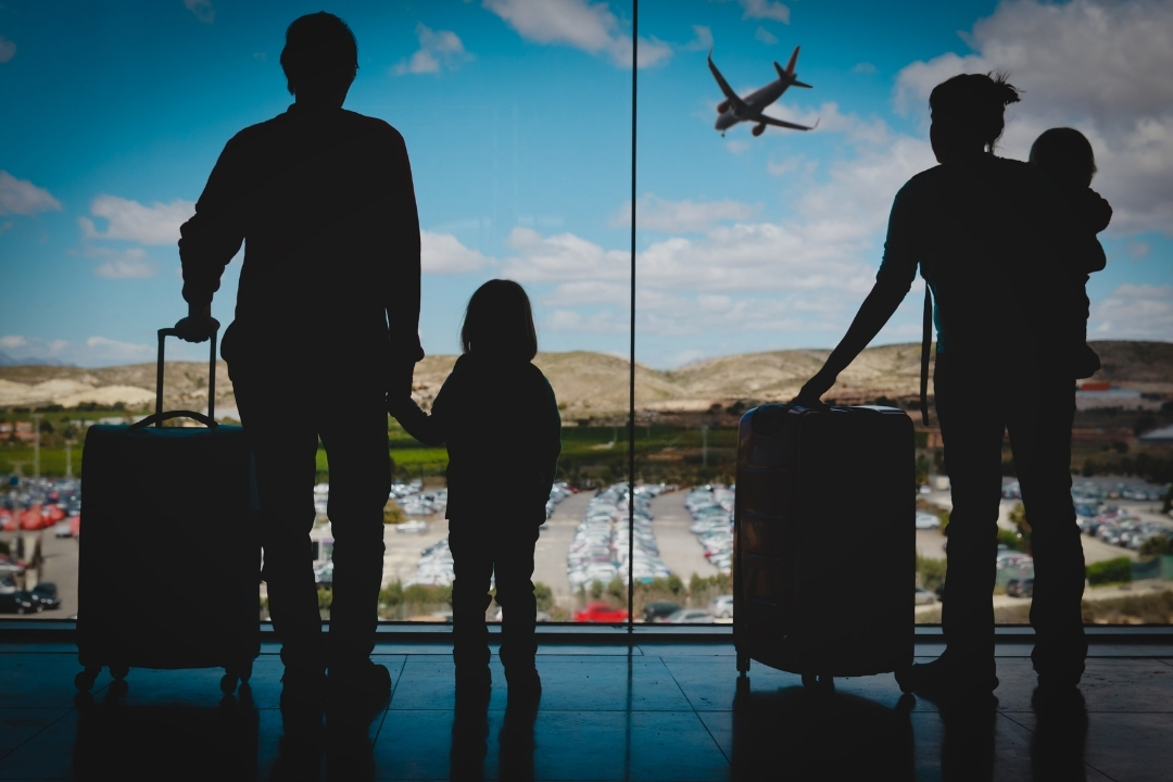 Silhoutte of family standing at airport with luggae looking out at planes - family airline reviews
