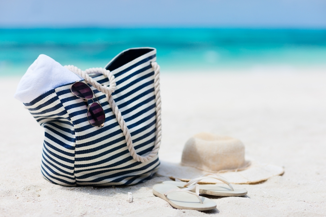 A large beach bag and sun hat sitting on the beach