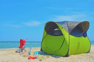 Green tent on a beach for families