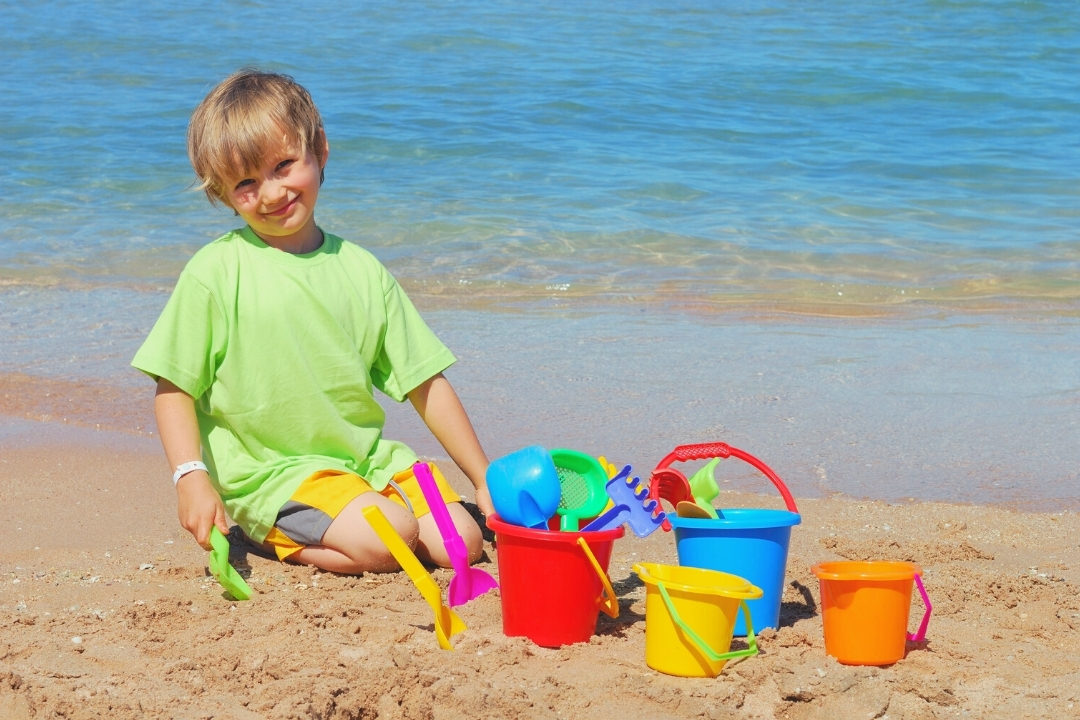Child playing with brightly coloured beach toys