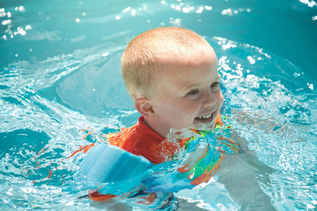 young child swimming with a puddle jumper flotation device