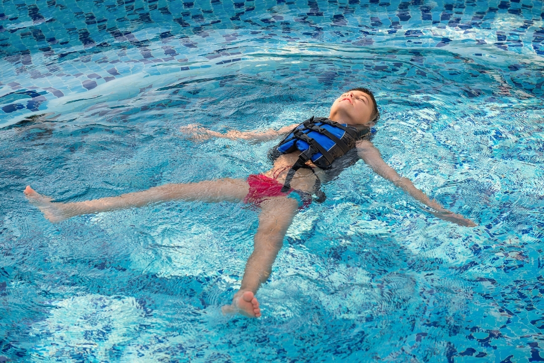 Child floating on their back in a pool wearing a swim vest floatation device