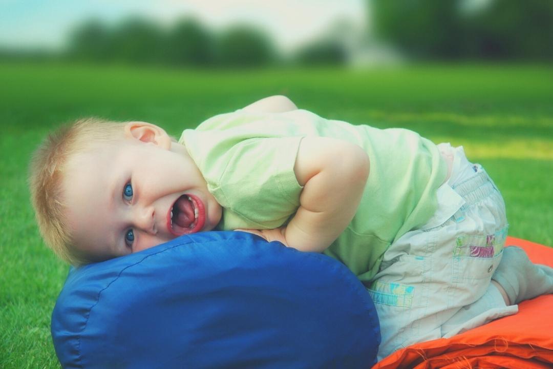 Toddler smiling lying on a sleeping bag camping