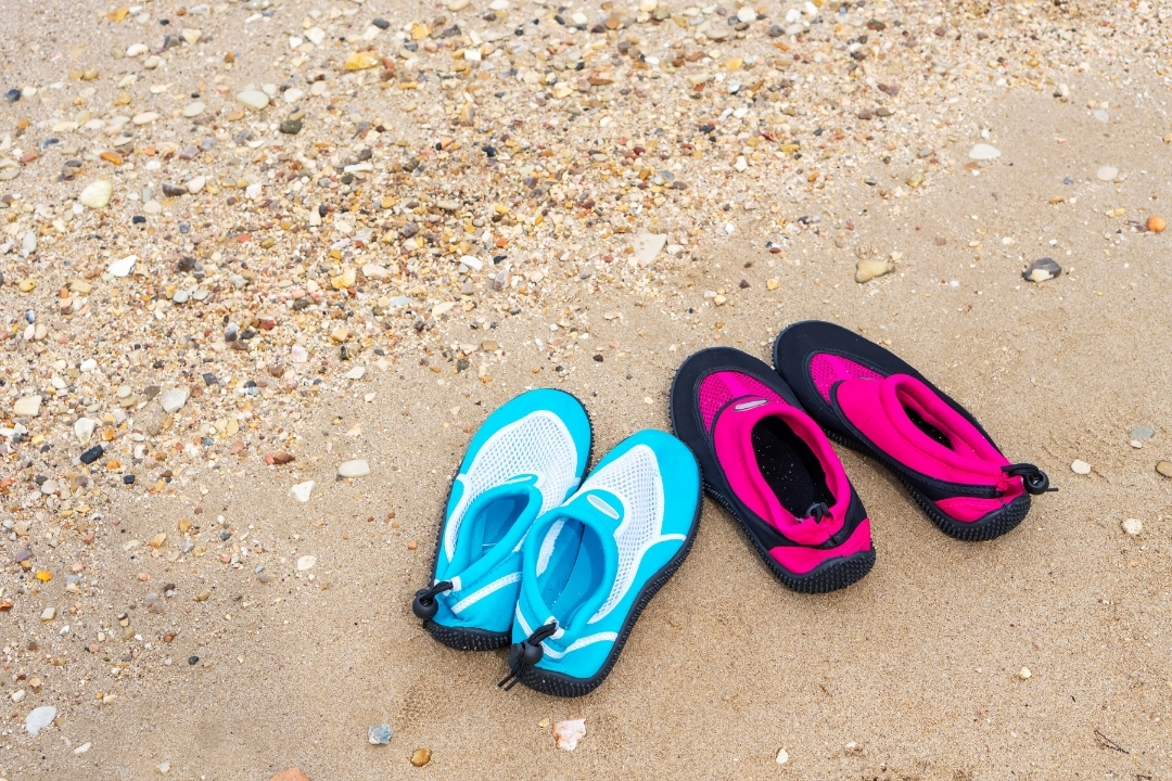 2 pairs of blue and pink water shoes for kids on a beach