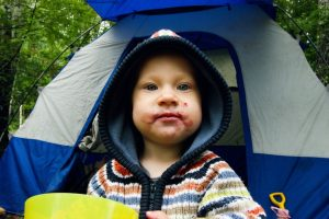 Infant camping grubby face in front of a tent