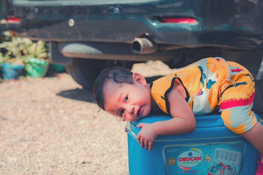 Toddler lying on top of a suitcase in front of a car ready for a road trip