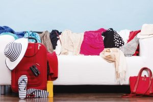 messy white couch covered in clothing getting orgnaised to pack