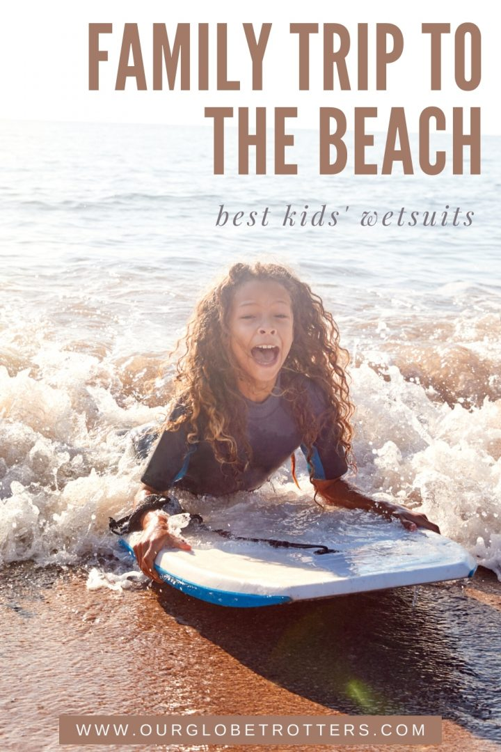 Girl squealing with delight as a wave crashes in her wetsuit and boogie board - caption Family Trip to the Beach Best Kids Wetsuits